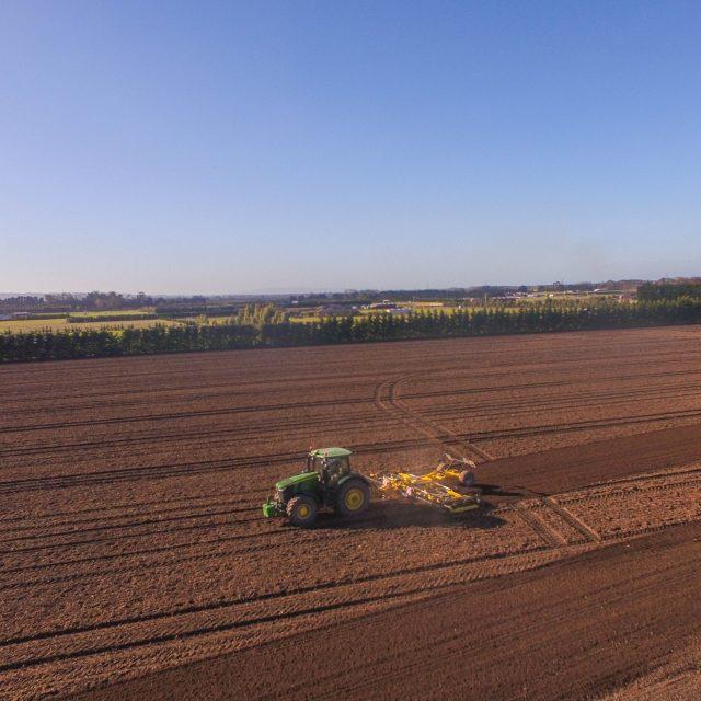 John Deere 7310R and 8 metre set of Bednar cultivators working down paddock